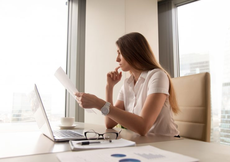 Pensive businesswoman reading document in office