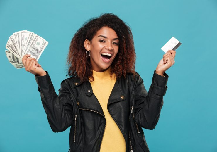 Happy african woman in leather jacket holding money