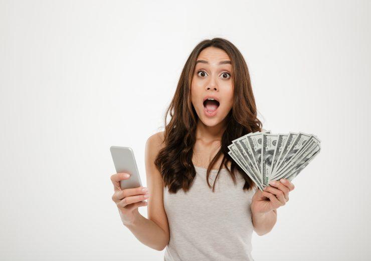 Portrait of attractive brunette female 30s winning lots of money