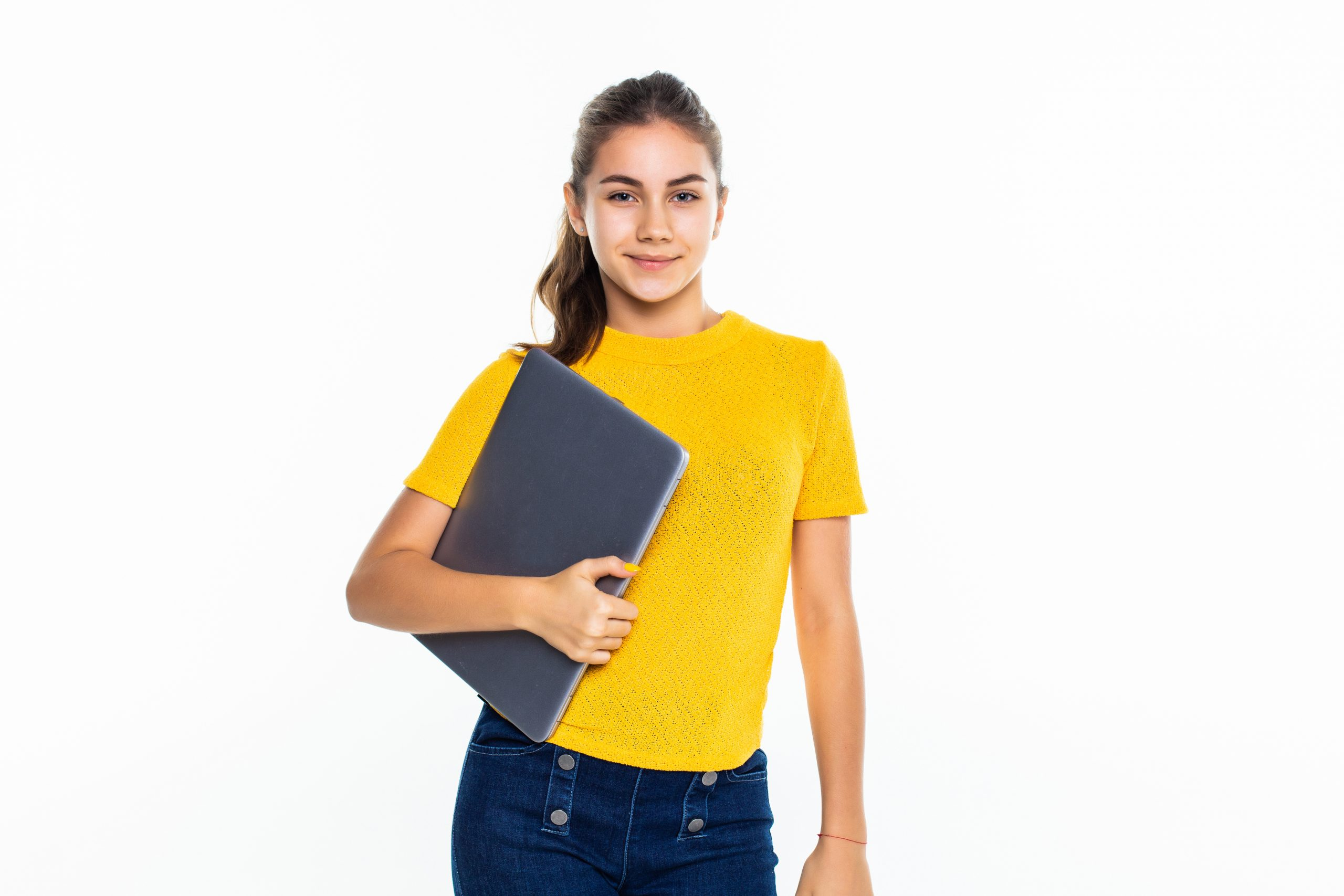 Smiling cute teen girl using laptop over white background