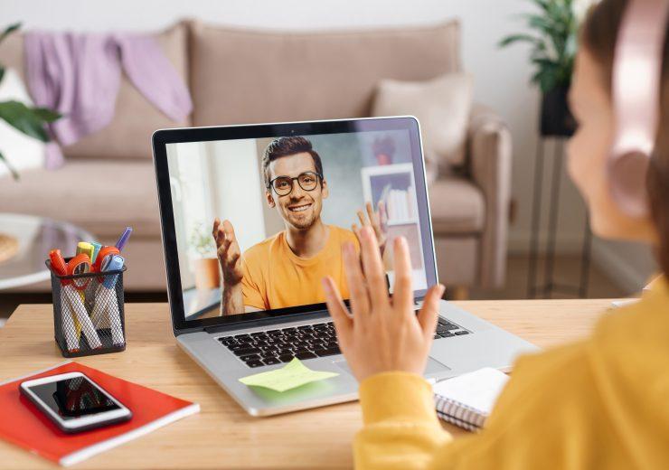 Girl in headphones waving hand to online teacher