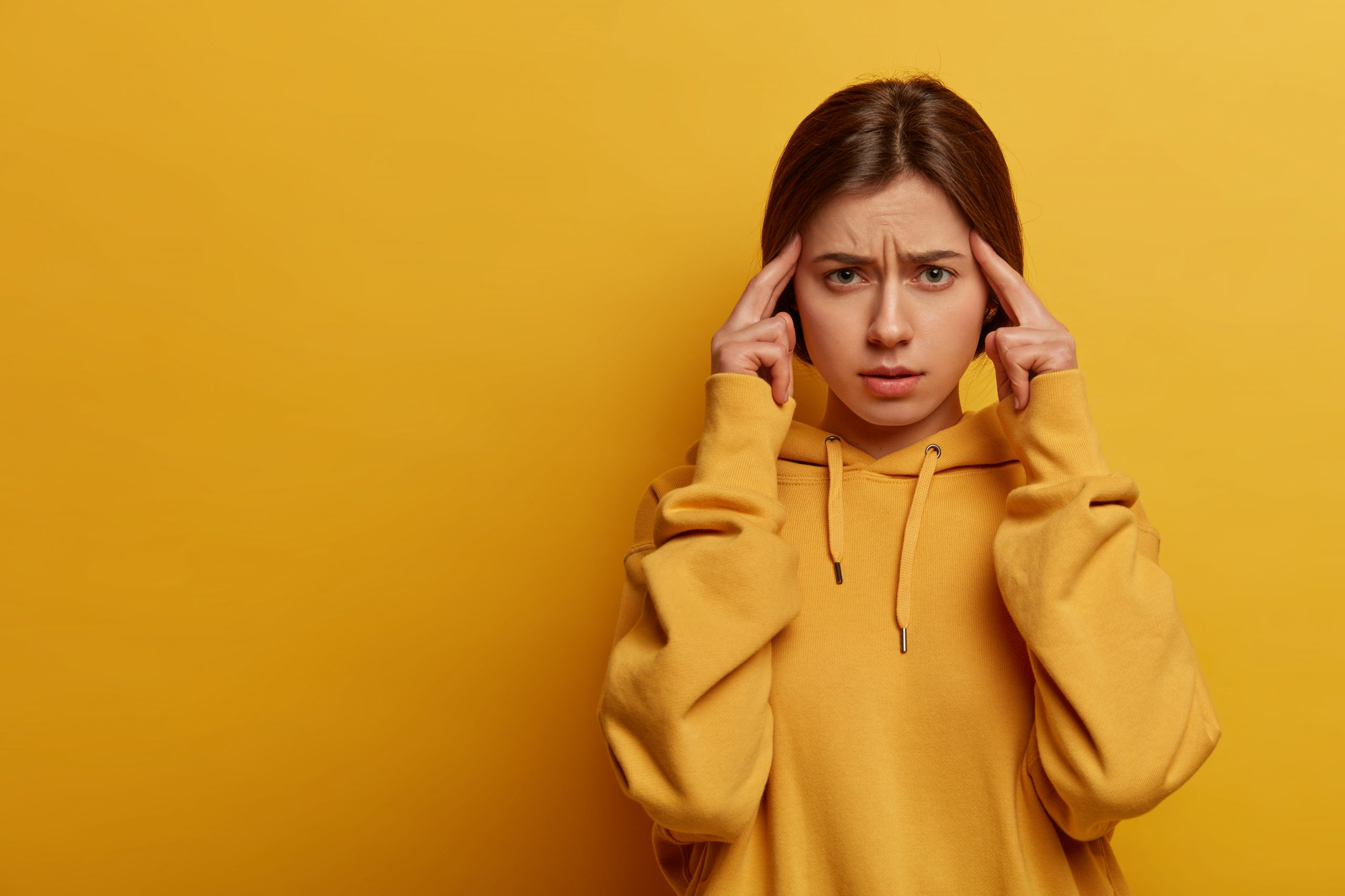 Frustrated displeased woman touches temples with index fingers, focus on something and thinks up idea, tries to make serious decision, suffers from headache, wears sweatshirt, isolated on yellow wall