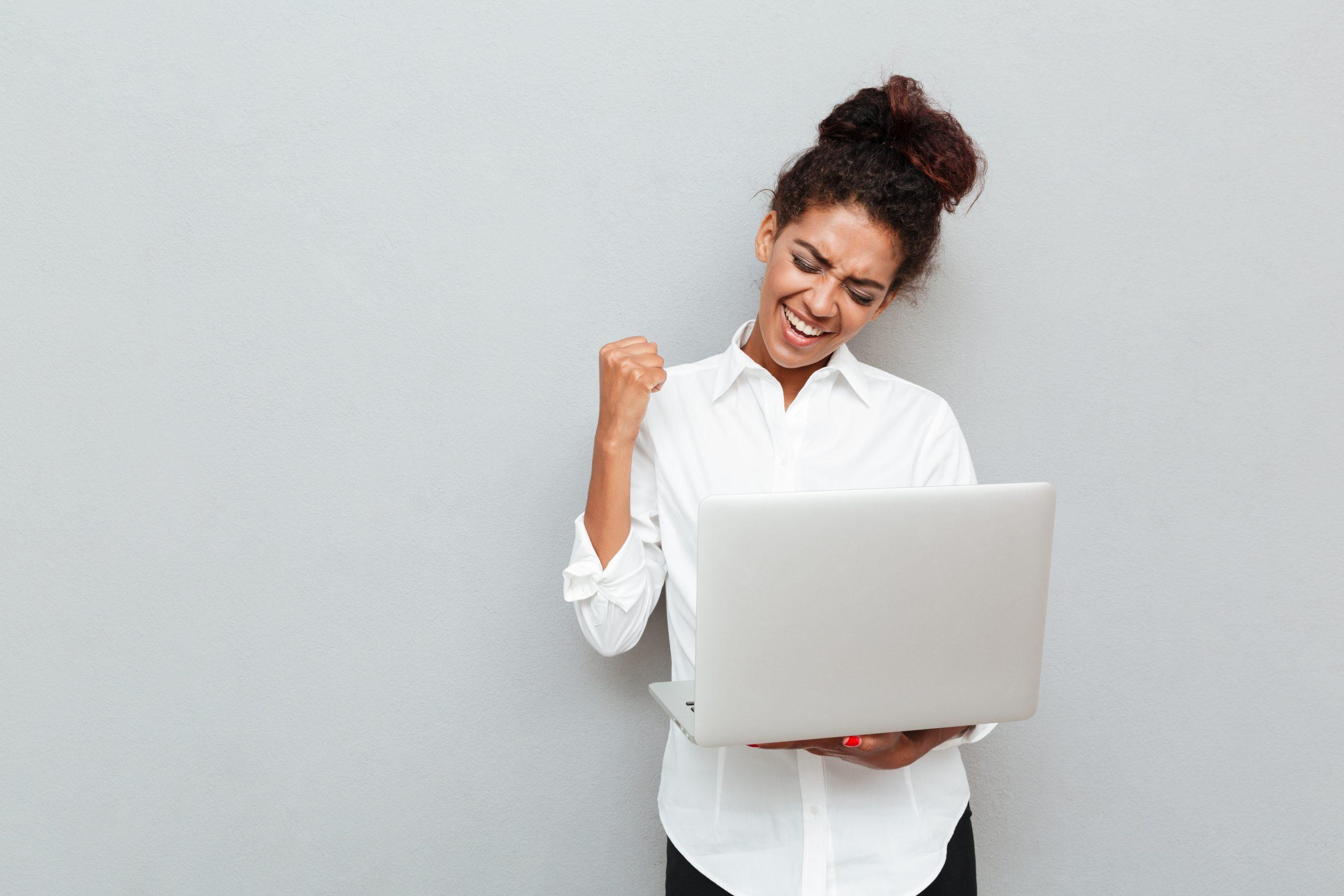 Cheerful business woman make winner gesture.